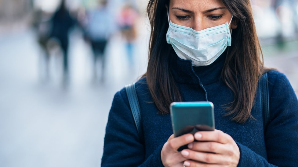 woman wearing face mask, holding phone