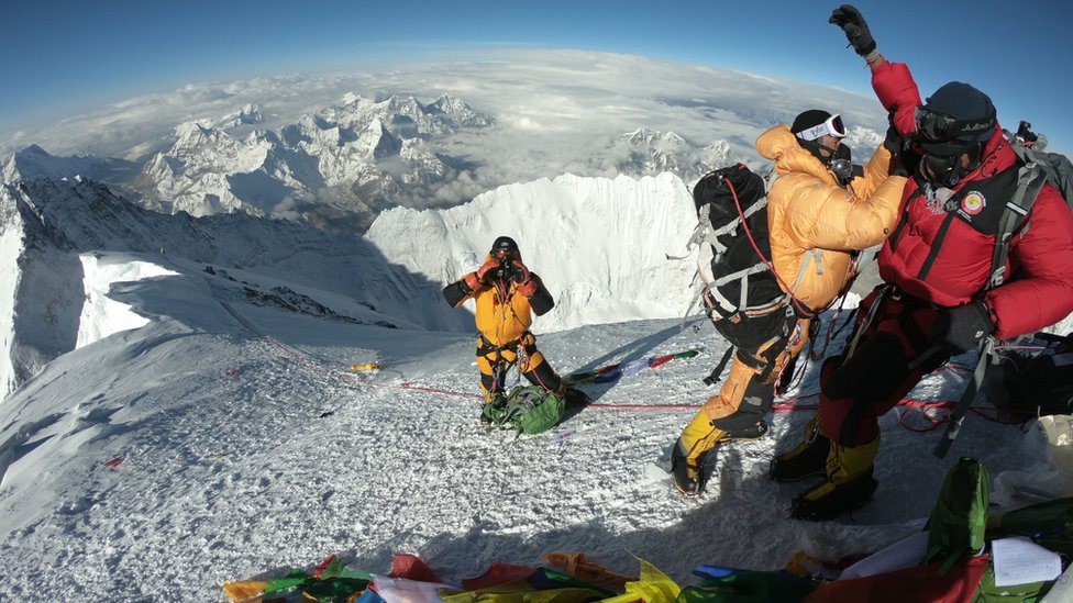 Sherpas and climbers standing on the summit of Everest