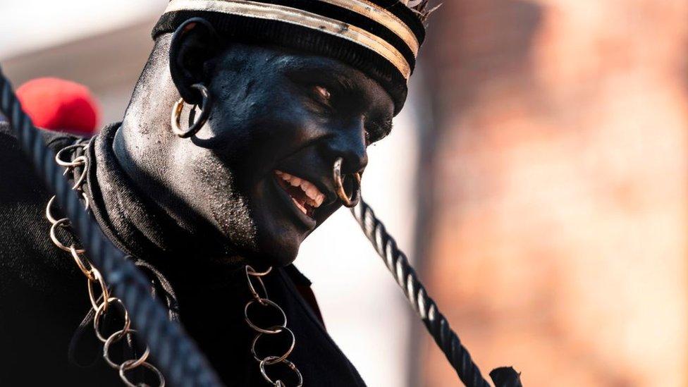 """En el festival folclórico belga Ducasse un hombre se pinta la cara de negro para representar al """"salvaje""""."""