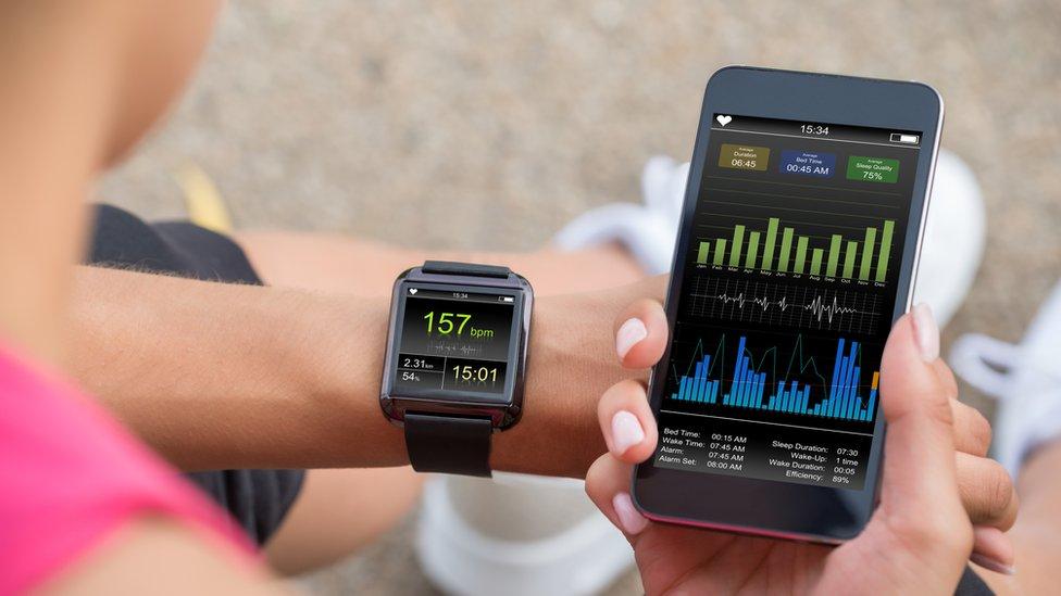 Mujer observa su pulsera inteligente y aplicación de pulso cardíaco en su teléfono