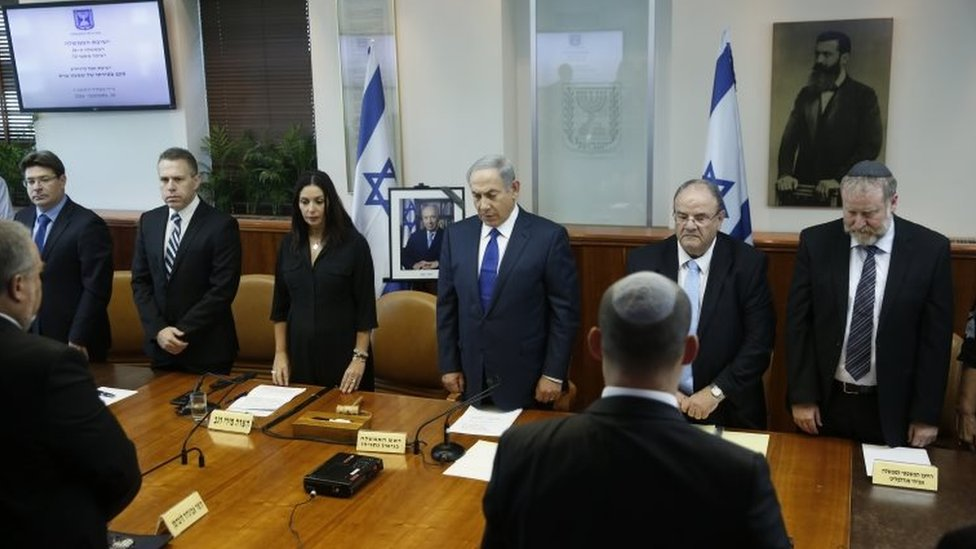 Israeli Prime Minister Benjamin Netanyahu, centre, and his cabinet ministers observe a moment of silence during a special cabinet meeting to mourn the death of former Israeli President Shimon Peres, in Jerusalem, Wednesday, Sept. 28, 201