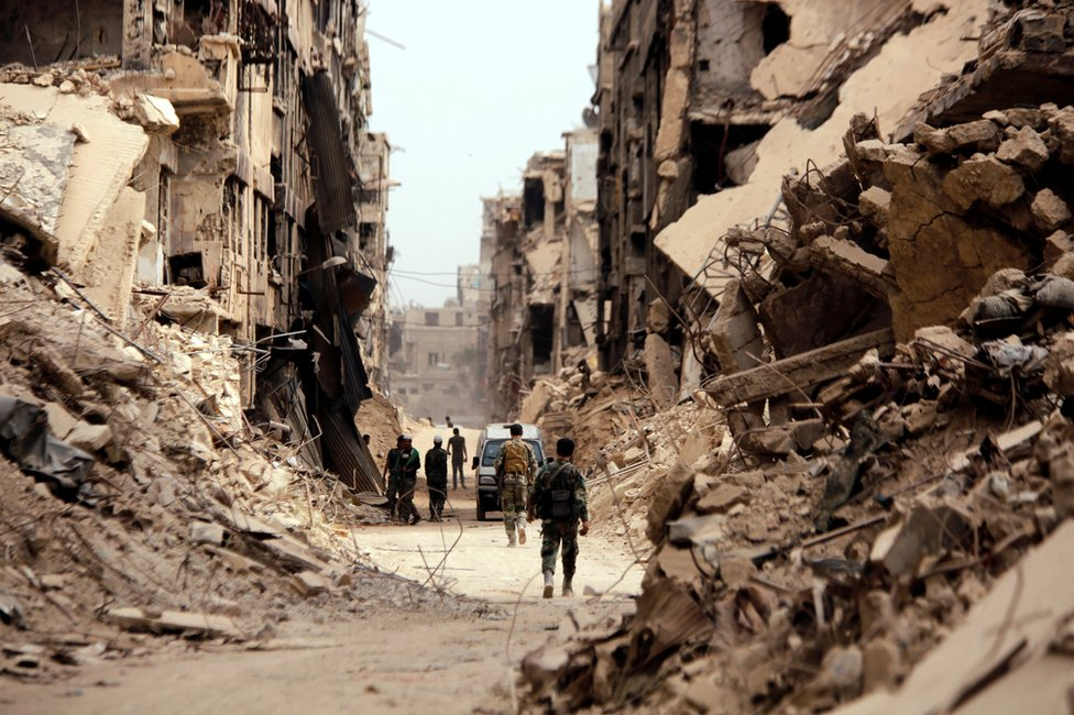 جنود يسيرون بجوار المباني المهدمة في مخيم اليرموك للاجئين الفلسطينيين في العاصمة السورية دمشق