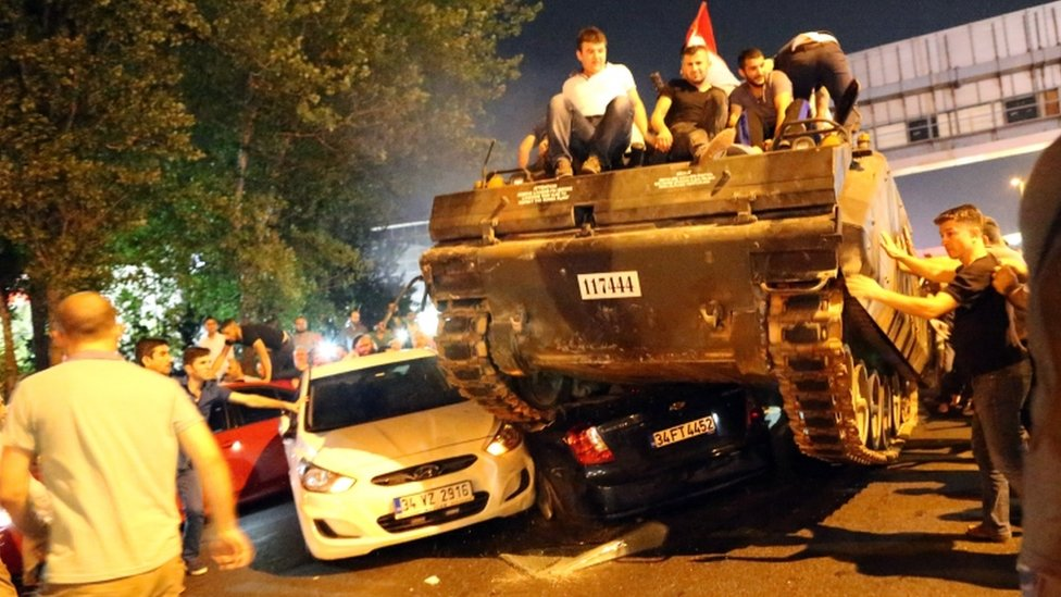 Turkish men sitting on a tank as it runs over cars, Istanbul, Turkey, July 2016