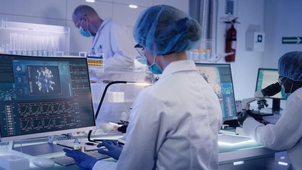 Cientistas num laboratório mexem em computadores e microscópios