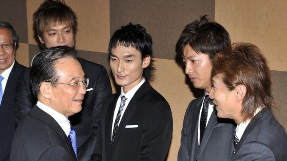 Visiting Chinese Prime Minister Wen Jiabao (L) shakes hands with Japanese pop group SMAP