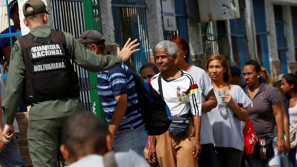 A Venezuelan soldier controls the crowd while people queue to try to buy cooking oil and margarine at a supermarket in Caracas on 12 July