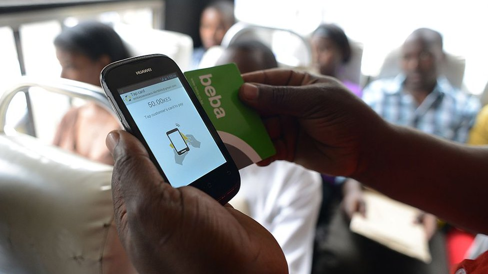 A Kenyan bus passenger uses a mobile phone-based money transfer service to pay their bus fare