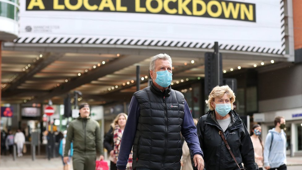 People wearing facemasks walking in Manchester