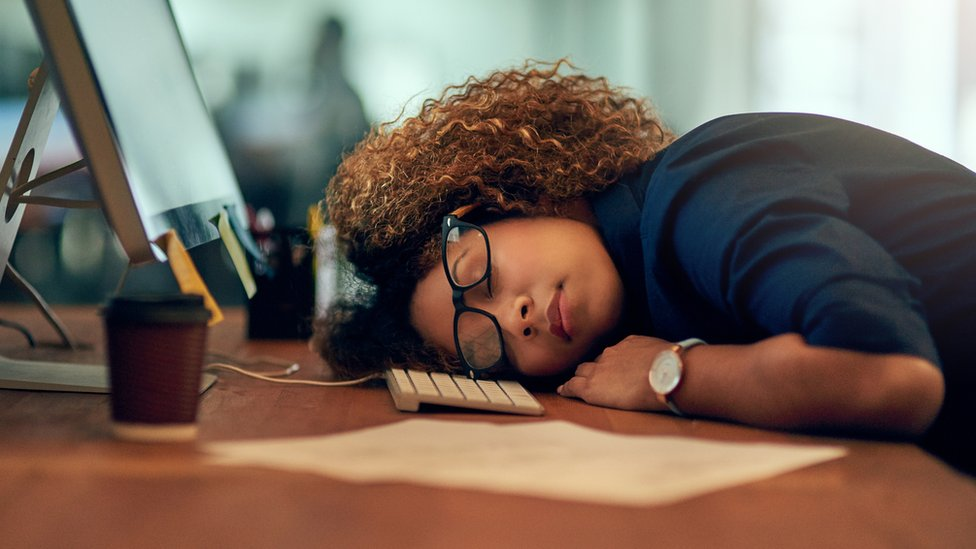 Mujer dormida delante del ordenador.