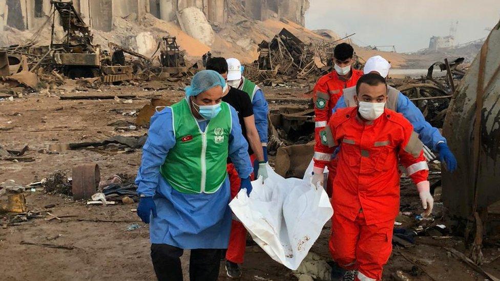 فريق انقاذ ينقل جثة من موقع الانفجار