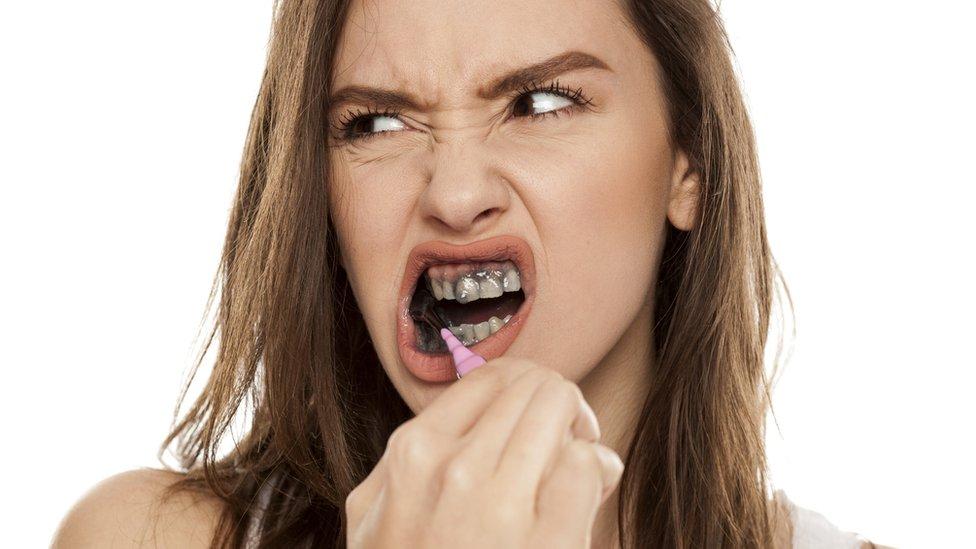 امرأة تنظف أسنانها بمعجون قائم على الفحم.