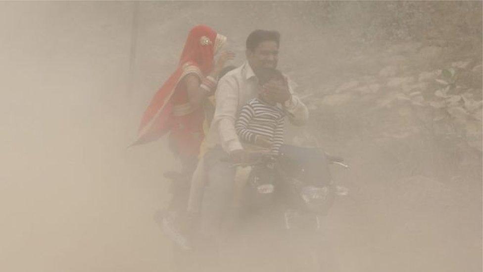 Батько, мати і дитина на моторолері в щільному диму