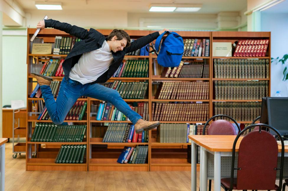 Un joven salta en una biblioteca
