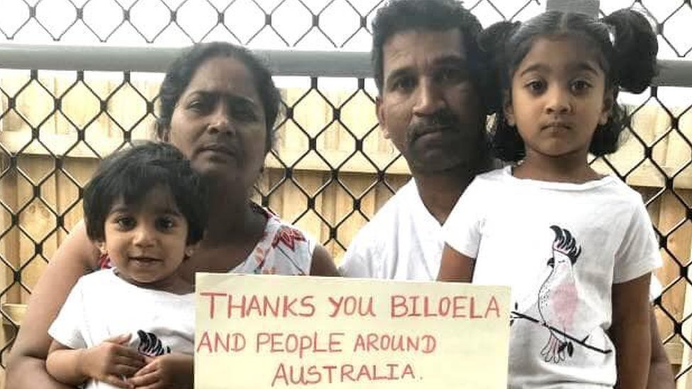 """A family picture of Nadesalingam and Priya and their two daughters holding a sign reading """"thanks you Biloela and people around Australia"""""""
