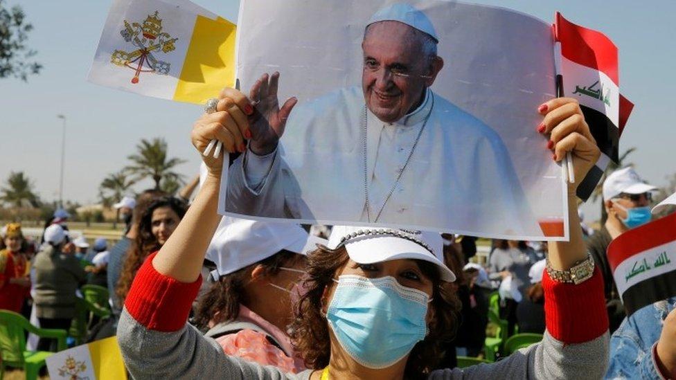 Mujer con foto del Papa fuera del aeropuerto de Bagdad el viernes 5 de marzo de 2020.