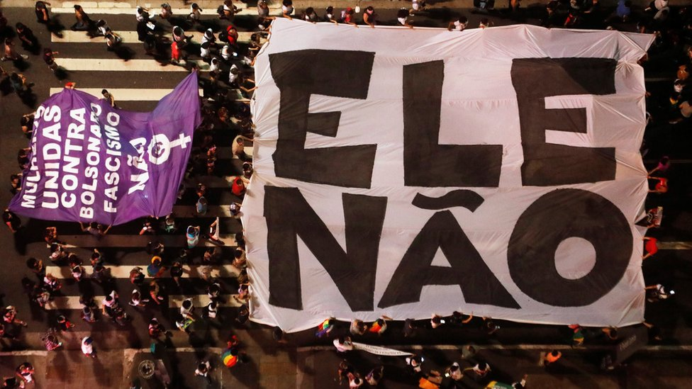 """Aerial view of protesters holding a large """"not him"""" banner in Sao Paulo"""
