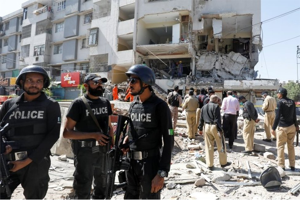 Police officers secure the site after an explosion in the multi-storey residential building in Karachi, Pakistan October 21, 2020.