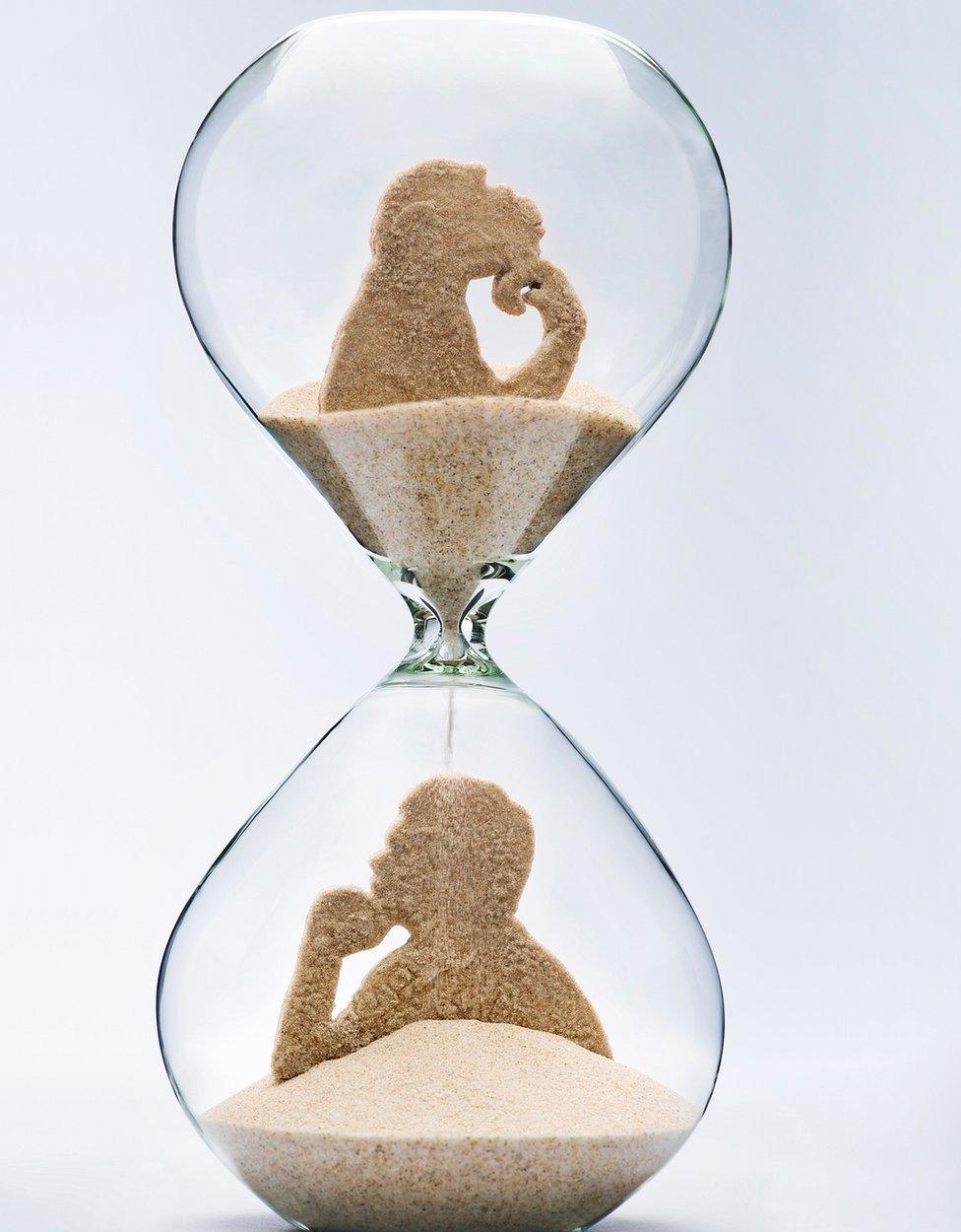 Reloj de arena con figura de mono arriba y de hombre abajo