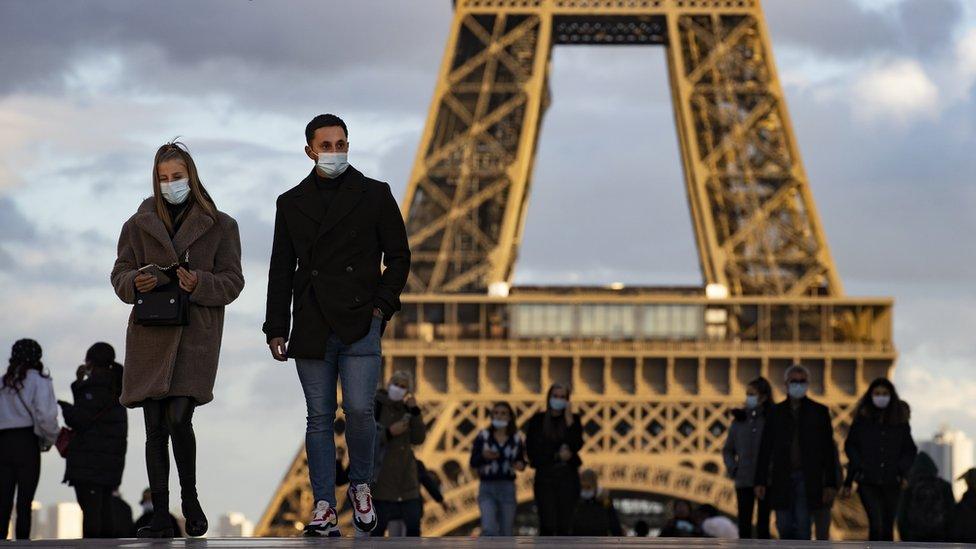 People wear masks near the Eiffel Tower in Paris