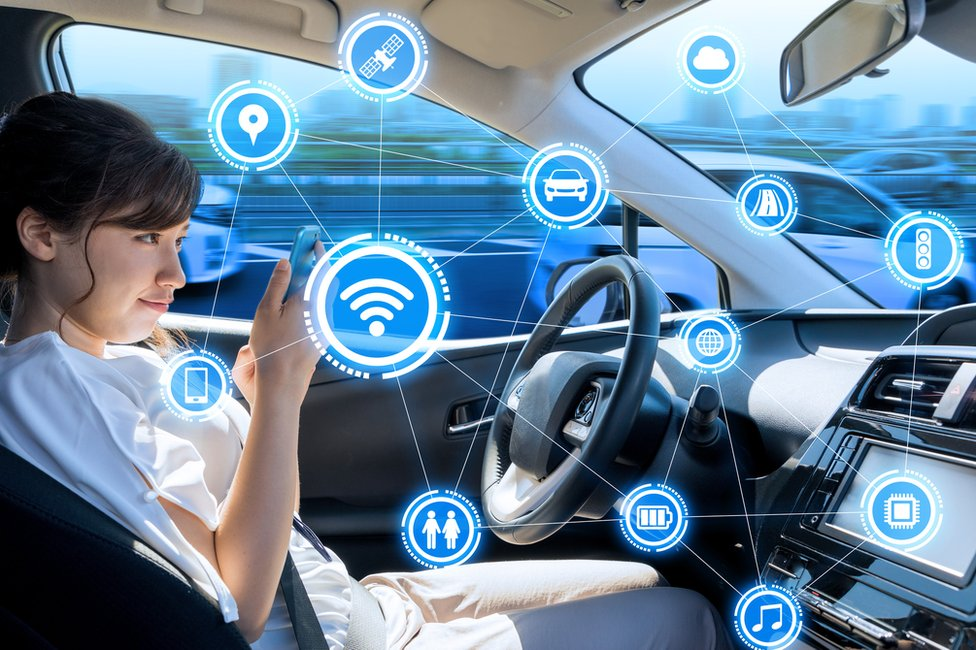 Young woman checking smartphone in self-driving car