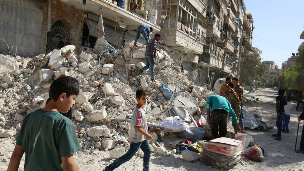 People remove belongings after an air strike in the rebel-held Qaterji district of Aleppo, Syria (17 October 2016)