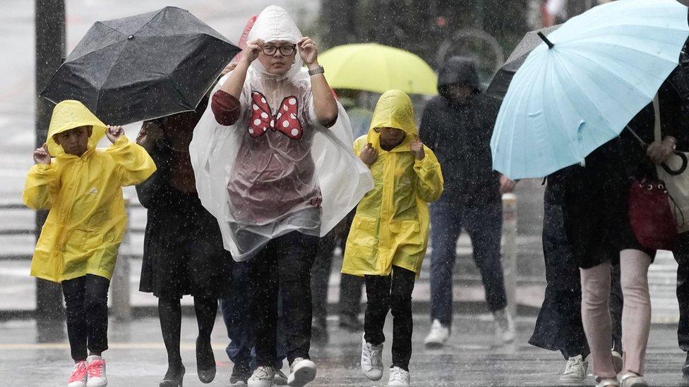 Pedestrians struggle against rain and wind in Tokyo, Japan, 12 October 2019