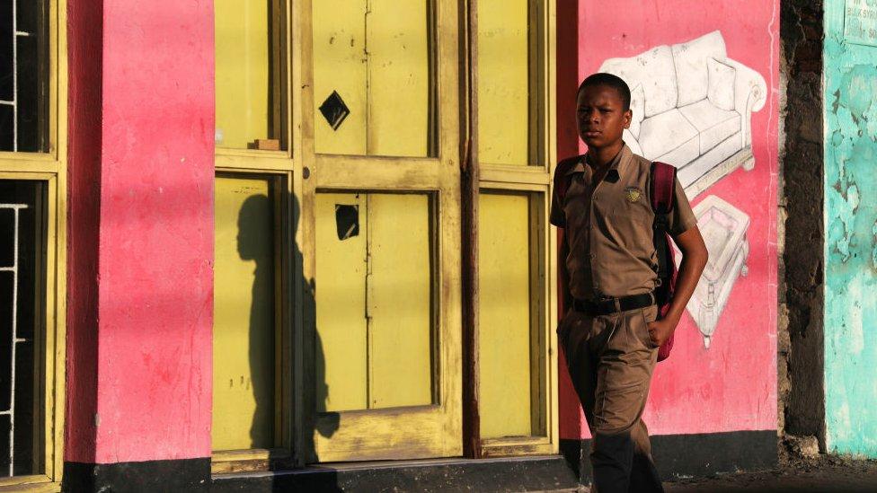 A boy walks in Kingston