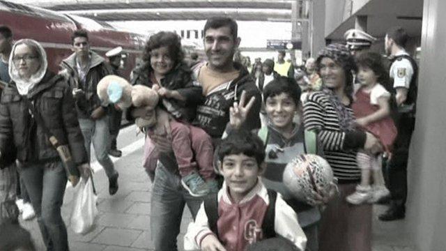 Refugees arrive on a station platform