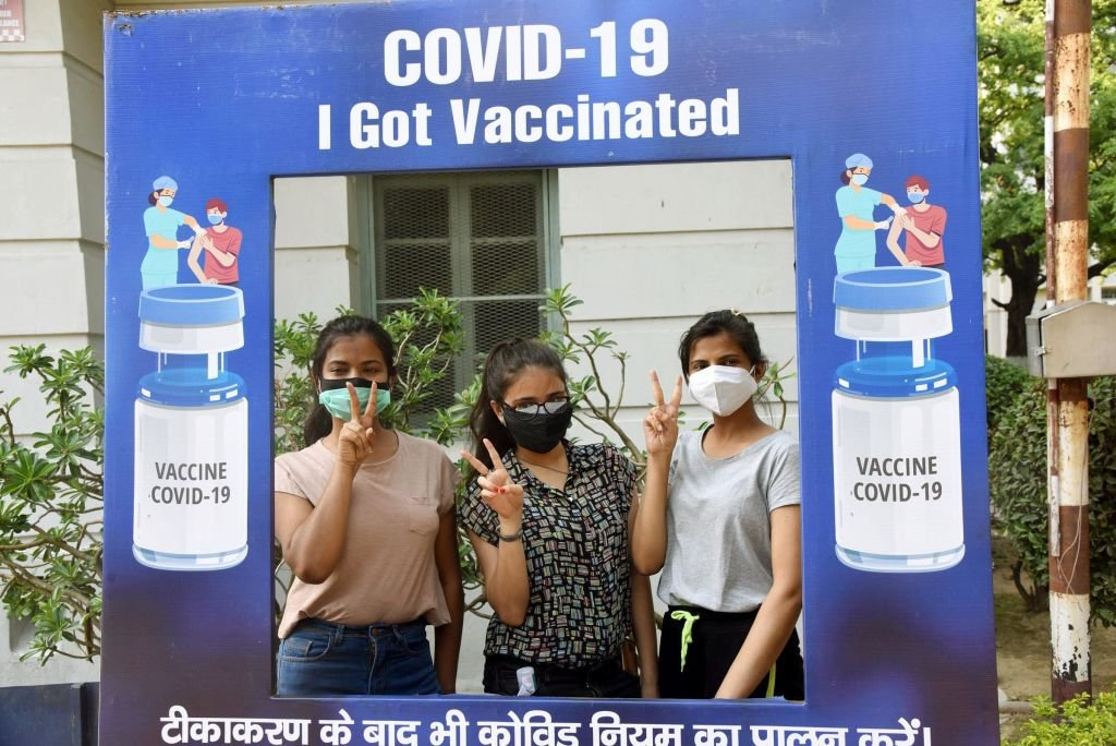 Young Indians pose after receiving their vaccinations