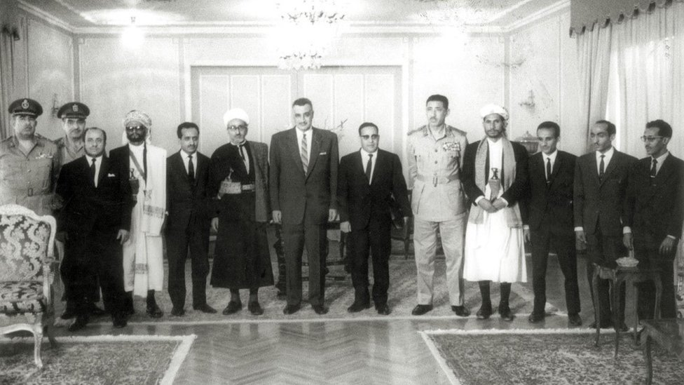 العيني متوسطاً عبدالحكيم عامر وعبدالناصر الذي يليه عبدالرحمن الإرياني رئيس اليمن الأسبق وحولهما عدد من كبار القادة اليمنيين والمصريين عام 1965