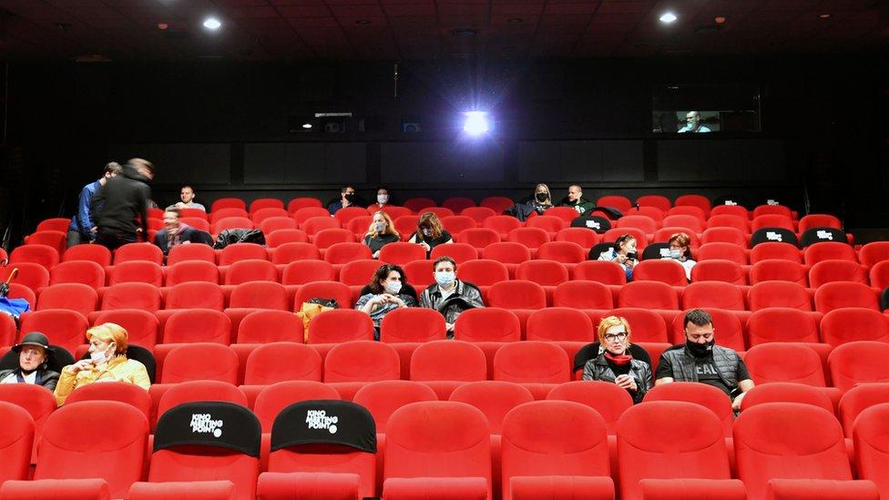 People in protective masks at a cinema in Sarajevo