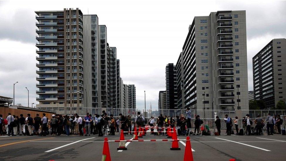 Cercas y cola de gente fuera de la Villa Olímpica
