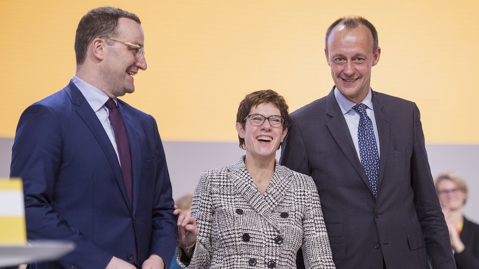 Annegret Kramp-Karrenbauer stands after receiving the most votes to become the next leader of the German Christian Democrats (CDU) between Jens Spahn (L) and Friedrich Merz (R)