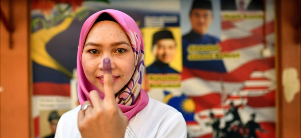 A woman shows her finger after voting in Malaysia