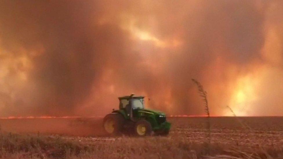 Un tractor delante de llamas y humo.