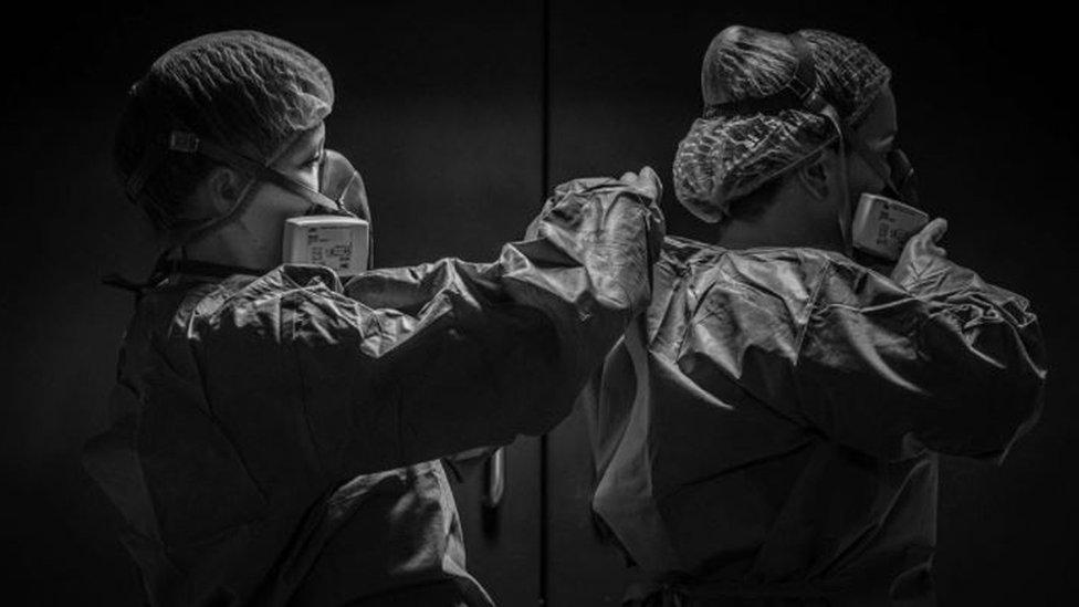 Foto de Emily Gilhespy mostra profissionais de saúde ajudando um ao outro a colocar EPI