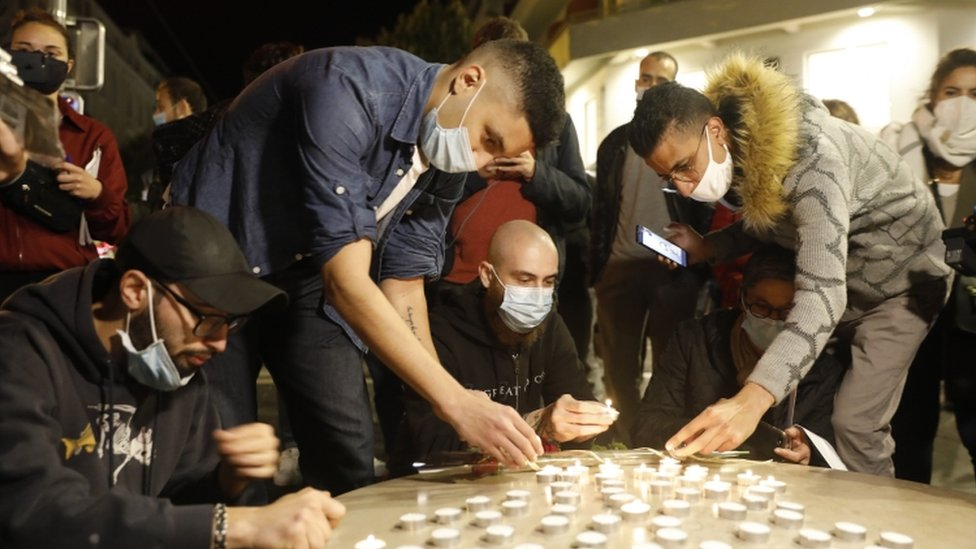 Young people light candles near the entrance of the Notre-Dame basilica church in Nice