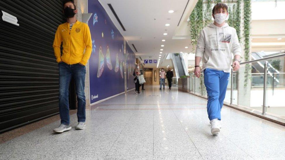 Alışveriş merkezinde maskeyle yürüyenler.