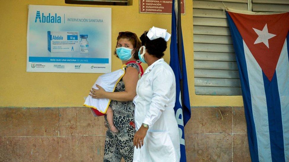 Mulher cubana com bebê ao lado de enfermeira em posto de vacinação em Cuba