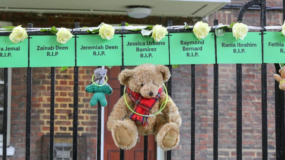 Osos de peluche colgados de una reja con carteles de los nombres de niños que murieron en la tragedia de Grenfell