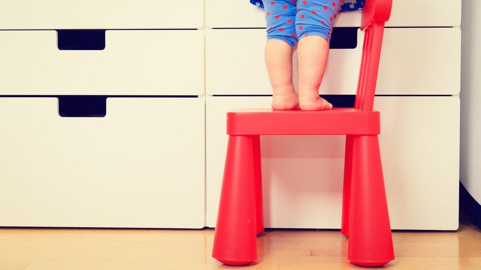 Niño de alrededor de dos años subido a una silla
