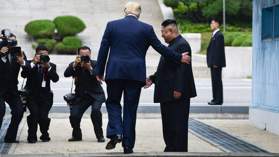 Trump cruzando hacia el lado norte de la línea divisoria entre las dos Coreas.