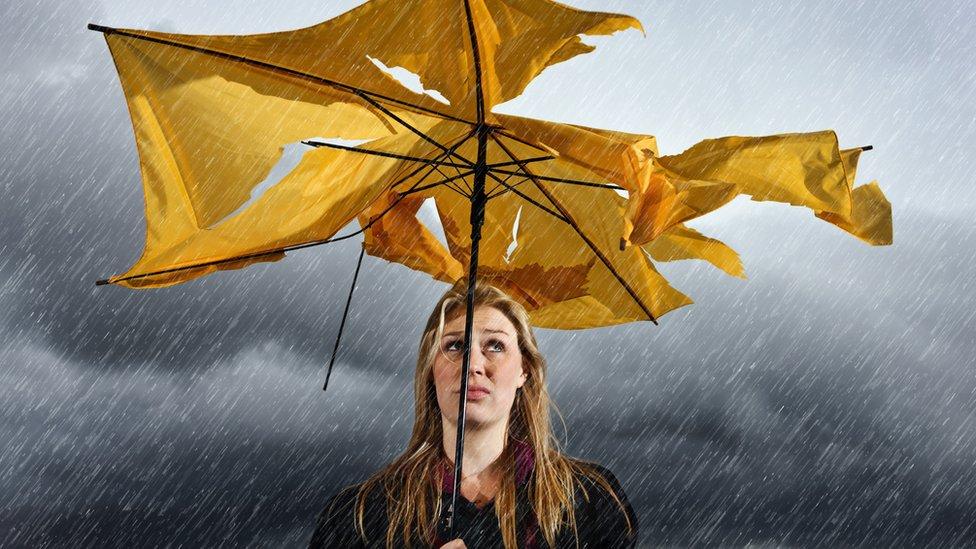 Mujer bajo la lluvia con paraguas roto