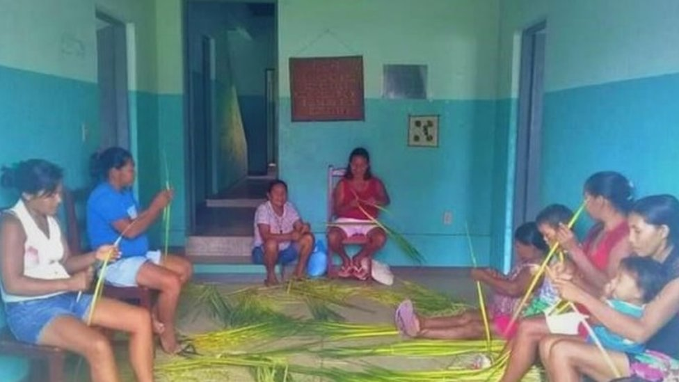 Mulheres indígenas se reunem para fazer artesanato