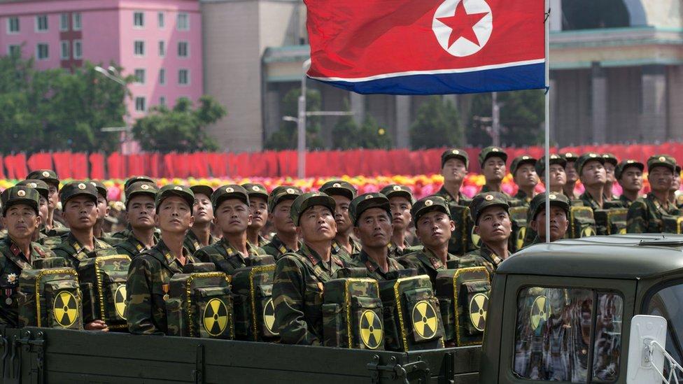 Prajurit Korea Utara membawa simbol nuklir dalam parade.
