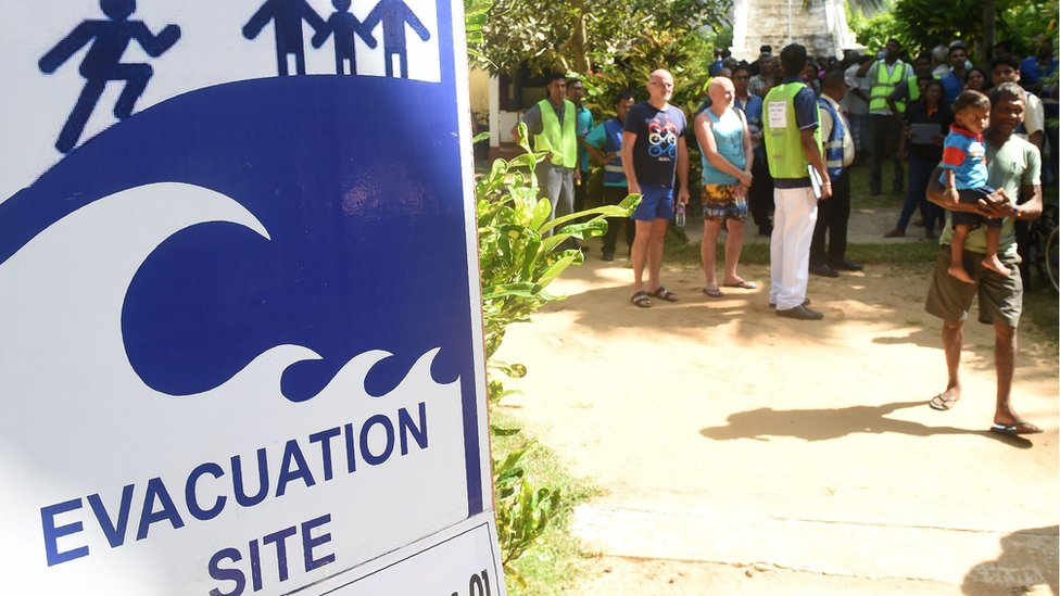 Tourists take part in a tsunami evacuation drill in Hikkaduwa on September 5, 2018