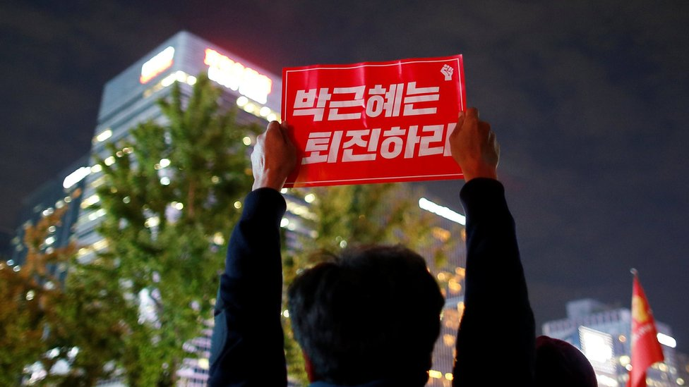 View of a sign being held up to the night sky by a protester in central Seoul, South Korea, 31 October 2016.