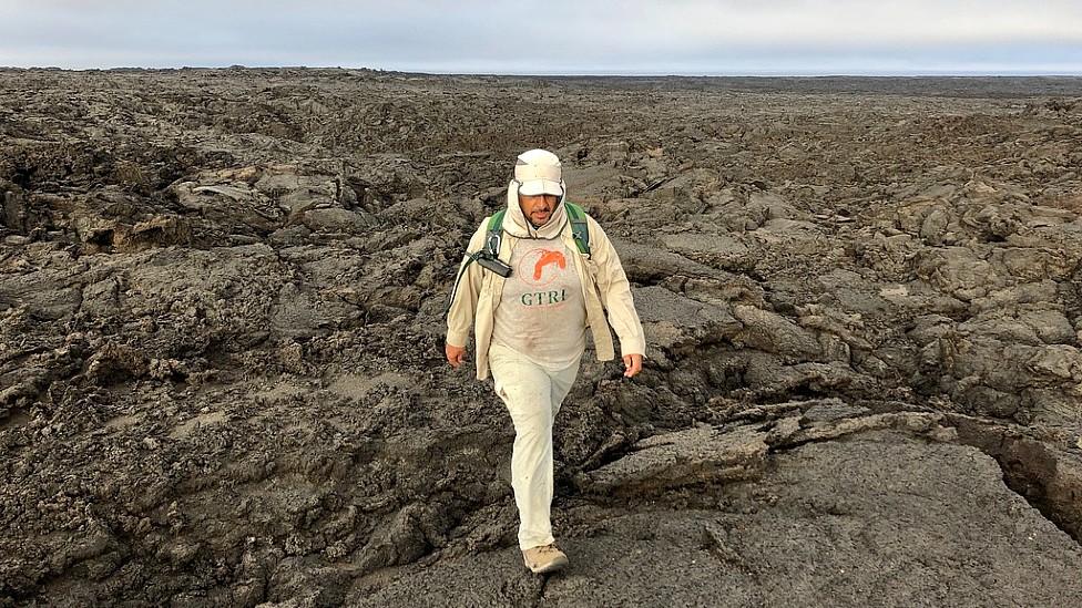 Washington Tapia caminando en los terrenos volcánicos de la Isla Fernandina