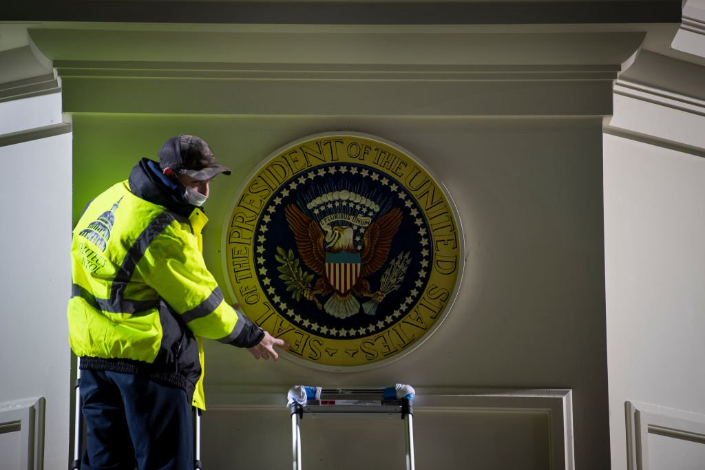 An Architect of the Capitol worker hangs up a Presidential seal