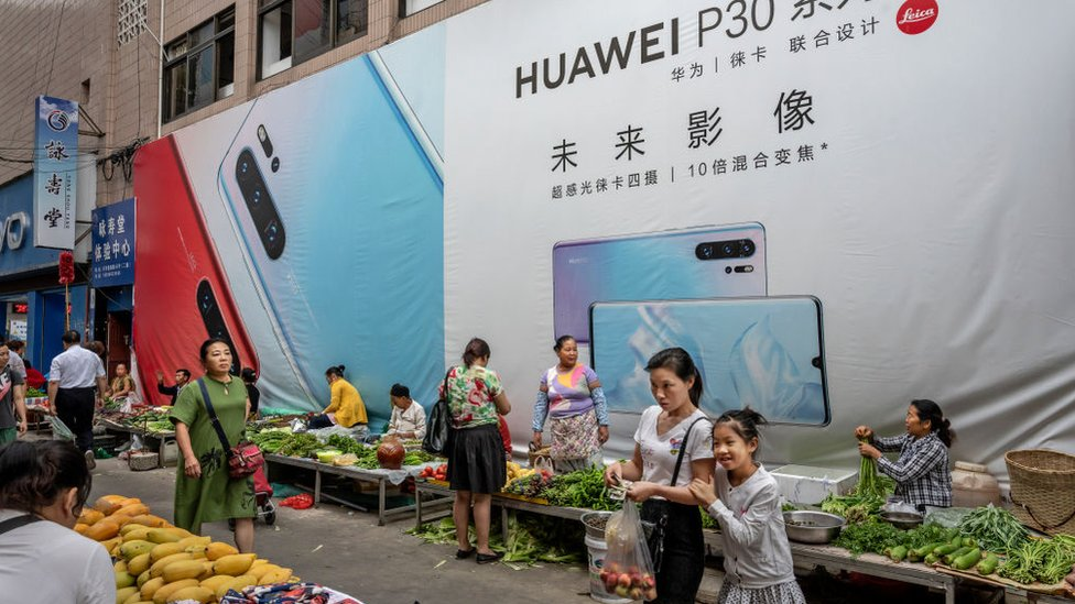A woman shops with her daughter in front of a billboard advertising smartphones for China's Huawei Technologies Co., at a market on June 1, 2019 in Mangshi, Yunnan Province, southwestern China.